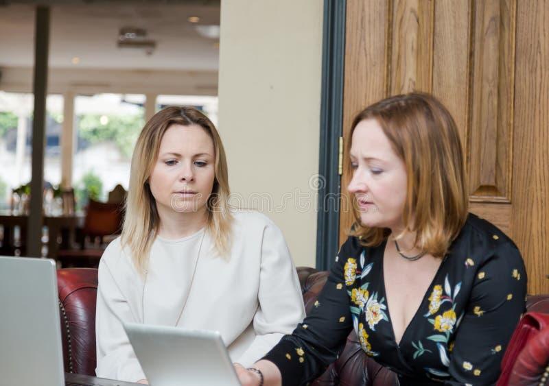 Mulheres de negócios novas que têm a conversação na reunião informal foto de stock royalty free