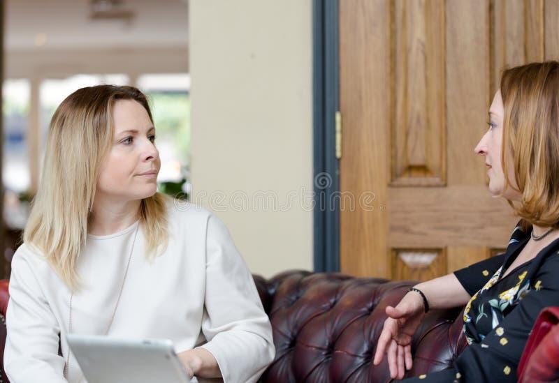 Mulheres de negócios novas que têm a conversação na reunião informal fotos de stock