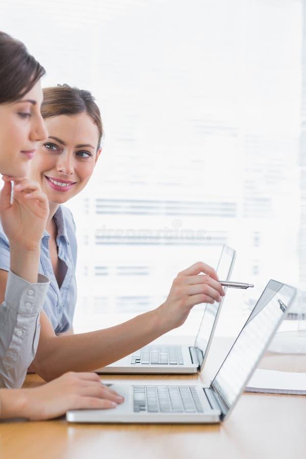 Mulheres de negócios novas que trabalham em seus portáteis fotografia de stock royalty free