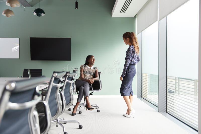 Mulheres de negócios ocasionalmente vestidas que têm a reunião informal na sala de reuniões moderna foto de stock royalty free
