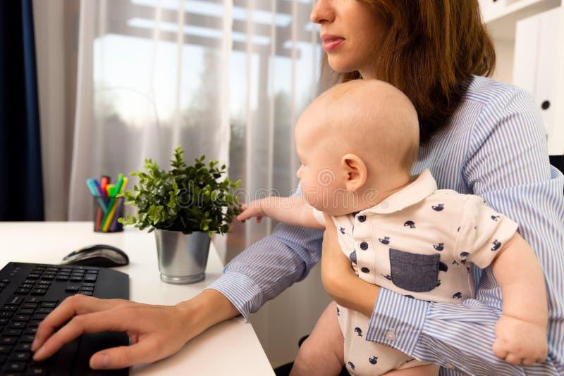 Mulheres de negócios ocupadas que trabalham em um escritório com um bebê em suas mãos imagem de stock