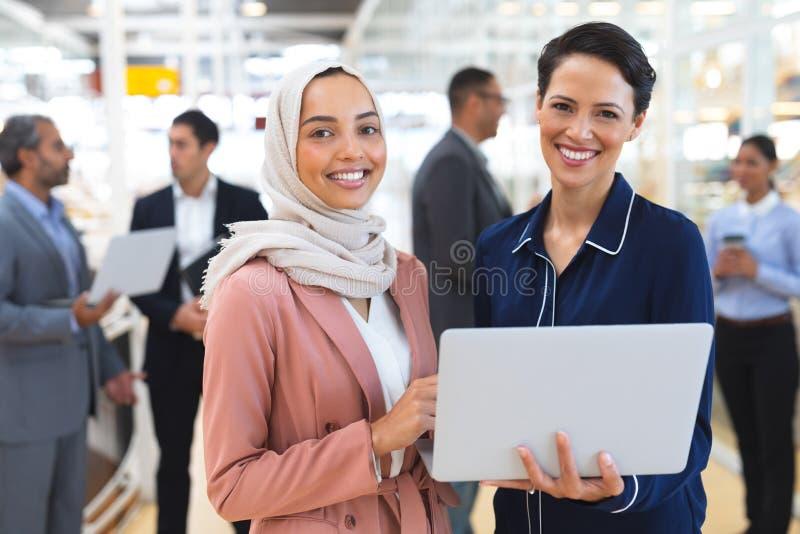 Mulheres de negócios olhando para a câmera enquanto trabalham em laptops em um escritório moderno fotografia de stock