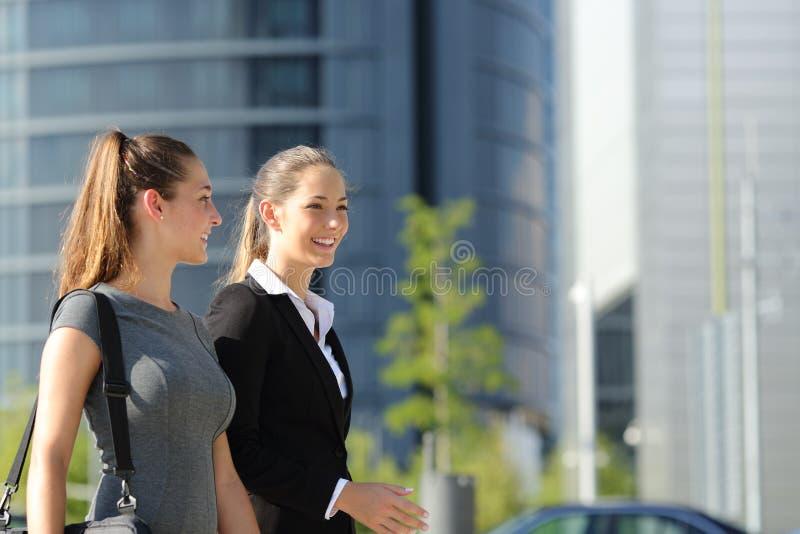 Mulheres de negócios que andam e que falam na rua fotos de stock royalty free