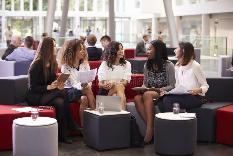 Mulheres de negócios que encontram-se na entrada ocupada do escritório moderno fotografia de stock royalty free