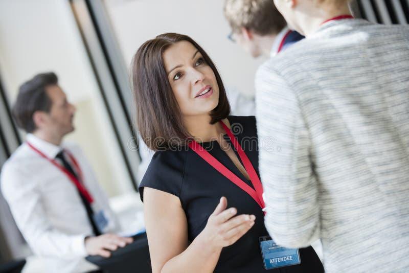 Mulheres de negócios que falam durante a ruptura de café no centro de convenções fotos de stock