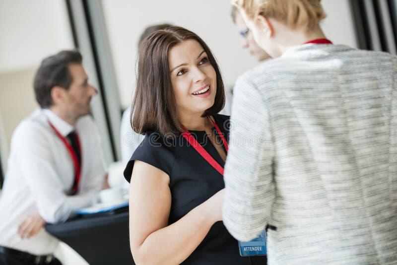 Mulheres de negócios que falam durante a ruptura de café no centro de convenções foto de stock