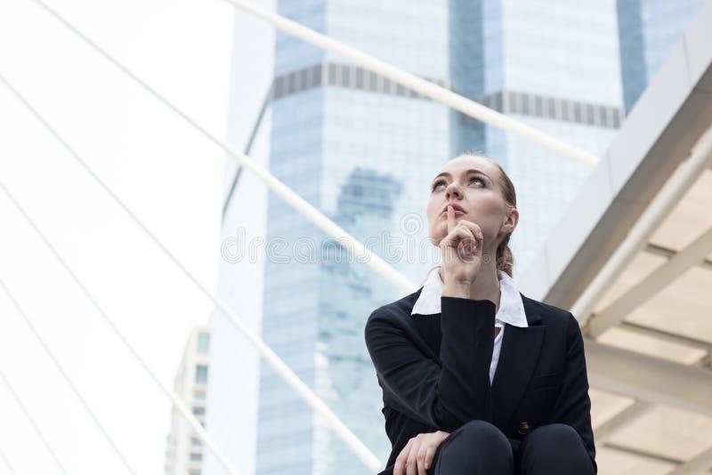 Mulheres de negócios que sentam-se na escada fora da construção e que pensam e imagem de stock
