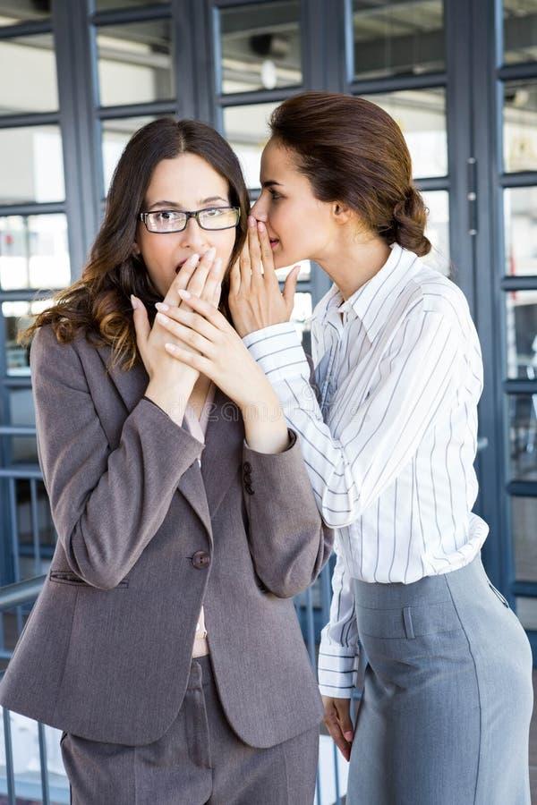 Mulheres de negócios que sussurram dentro a sua orelha do colega imagens de stock