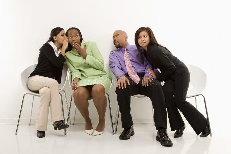Mulheres de negócios que sussurram quando outro eavesdrop. fotos de stock