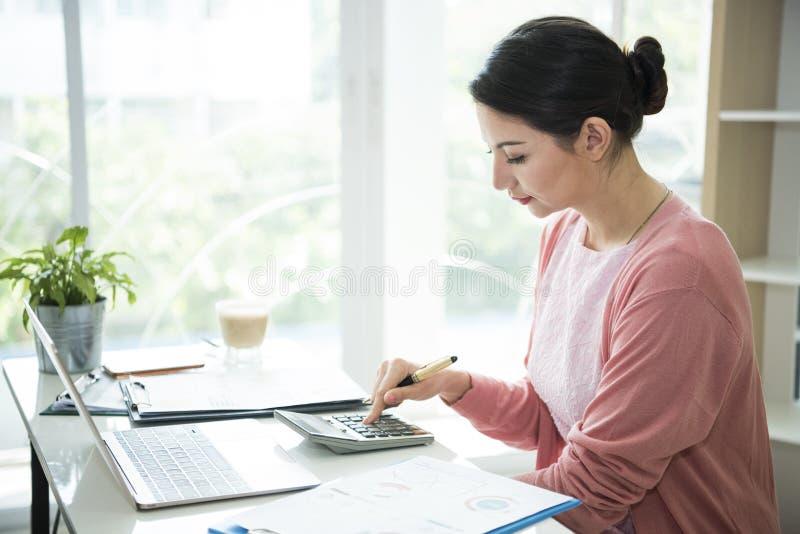 Mulheres de negócios que usam a calculadora com análise de figuras financeiras imagens de stock royalty free
