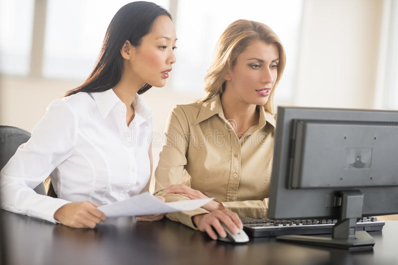 Mulheres de negócios que usam o computador de secretária fotos de stock