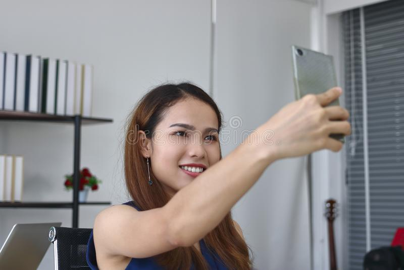 Mulheres de neg?cio asi?ticas novas de sorriso que tomam uma imagem ou um selfie no escrit?rio foto de stock royalty free