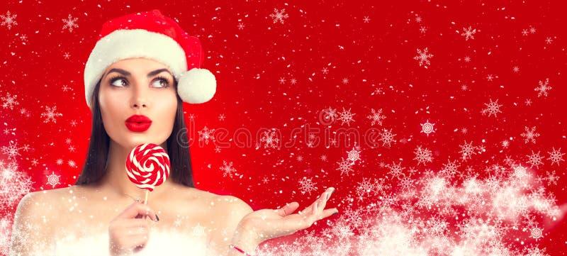 Mulheres de Santa com sacos Menina modelo alegre no chapéu de Santa com doces do pirulito que aponta a mão, propondo o produto Ex imagens de stock