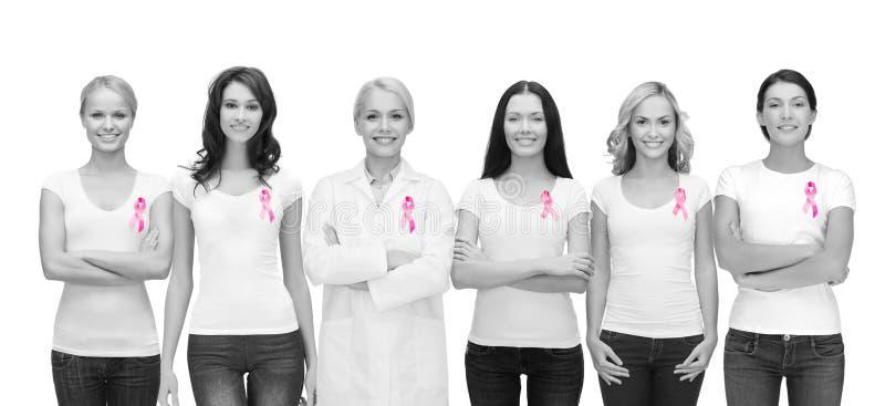 Mulheres de sorriso com as fitas cor-de-rosa da conscientização do câncer imagem de stock royalty free