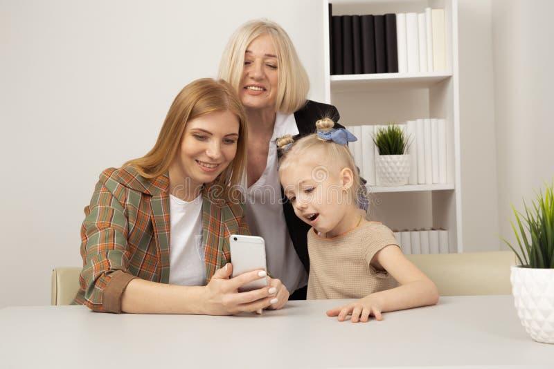 Mulheres de sorriso e telefone de observação da menina junto fotos de stock