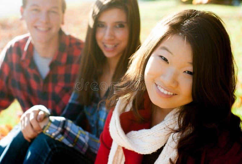 Mulheres de sorriso novas com amigos fotos de stock royalty free