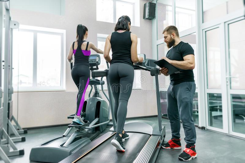Mulheres de sorriso novas da aptidão com instrutor pessoal um homem atlético adulto na escada rolante no gym Esporte, trabalhos d fotos de stock royalty free