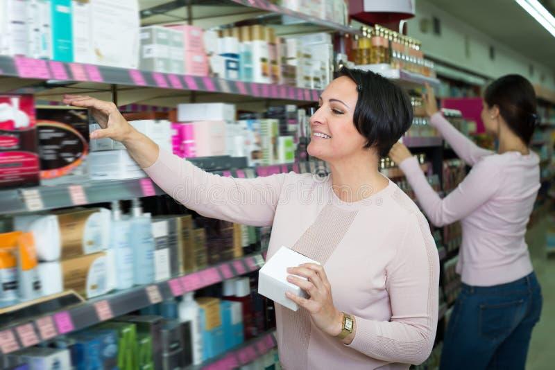 Mulheres de sorriso que escolhem o creme da prateleira fotografia de stock royalty free