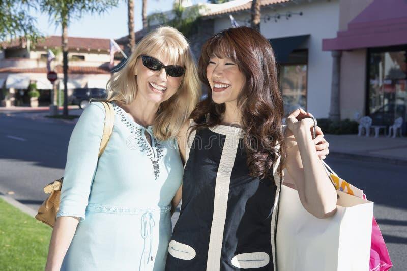 Mulheres de sorriso que estão de lado a lado prendendo sacos imagens de stock royalty free