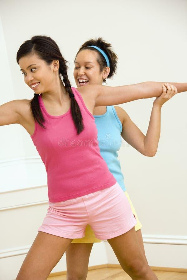 Mulheres de sorriso que fazem a ioga fotografia de stock royalty free