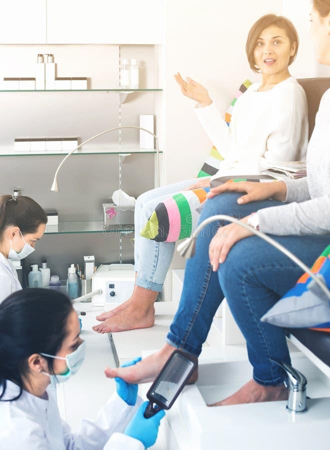 Mulheres de sorriso que obtêm o pedicure pelo profissional no salão de beleza foto de stock royalty free