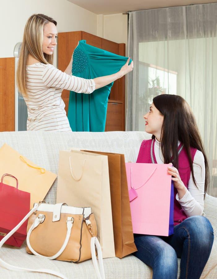 Mulheres de sorriso que olham o vestido novo em casa imagem de stock