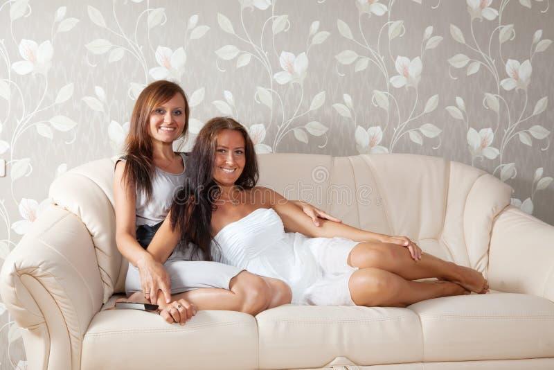 Mulheres de sorriso que sentam-se na sala de visitas imagem de stock