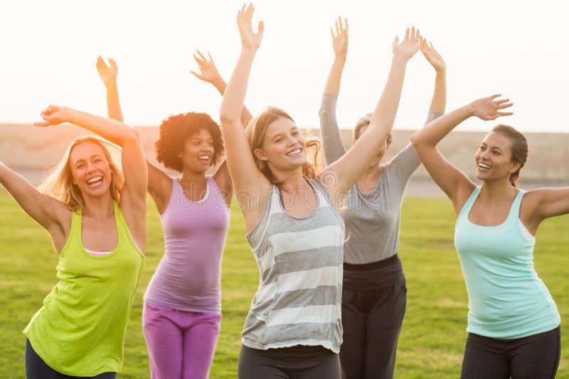Mulheres desportivas felizes que dançam durante a classe da aptidão fotos de stock royalty free