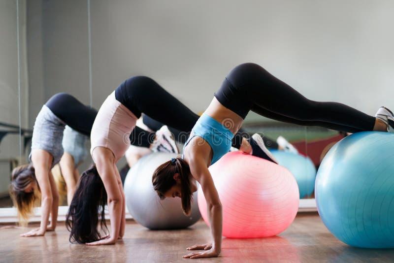 Mulheres desportivas que fazem o exerc?cio dos pilates em ajuste-bolas fotografia de stock royalty free