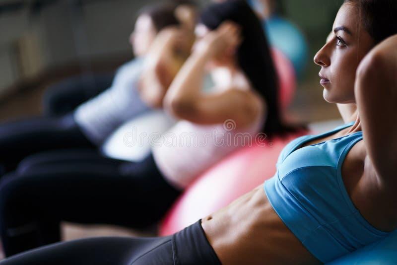 Mulheres desportivas que fazem o exerc?cio f?sico em ajuste-bolas imagem de stock royalty free