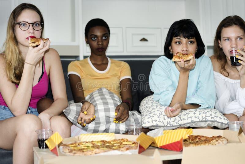 Mulheres diversas que sentam-se no sofá que come a pizza junto foto de stock royalty free