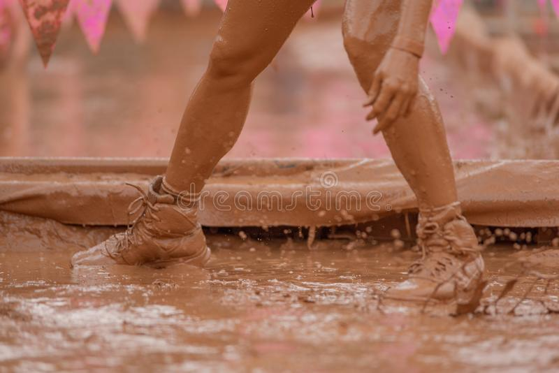 Mulheres do corredor de raça da lama que rastejam na lama sob obstáculos imagens de stock royalty free