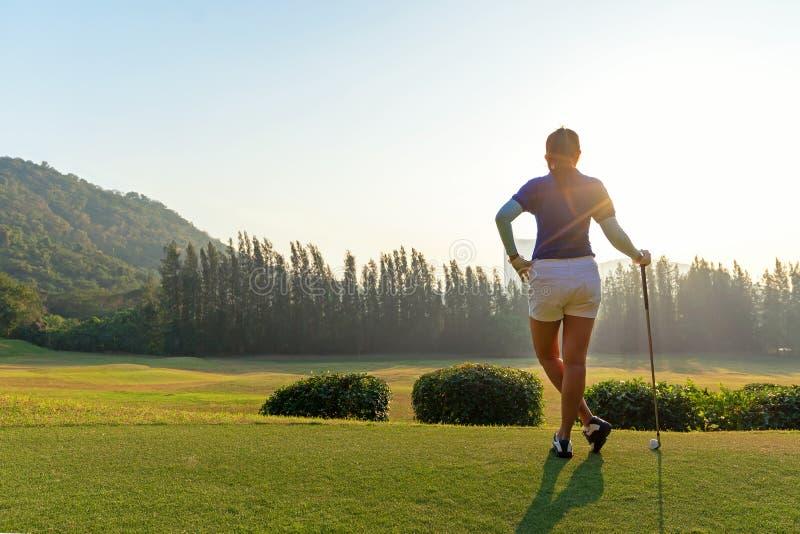 Mulheres do golfe Mulher de sorriso asiática feliz alegre com jogo do golfe no clube de golfe no tempo ensolarado e nivelando do  imagens de stock
