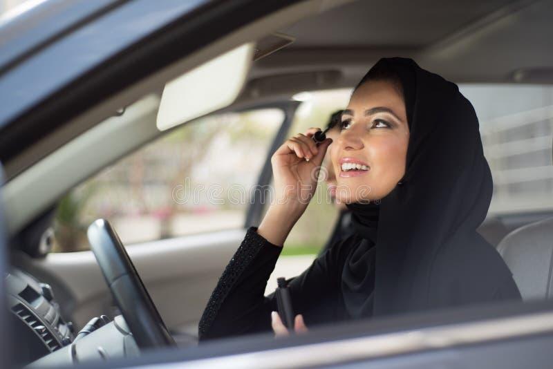 Mulheres do Oriente Médio que sentam-se dentro de um carro e que aplicam a composição foto de stock royalty free