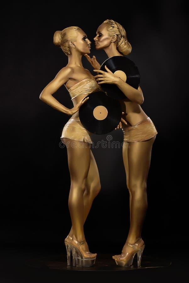 Futurismo. Faculdade criadora. Mulheres douradas lustrosas com registro de vinil sobre o preto. Bodyart dourado brilhante imagens de stock