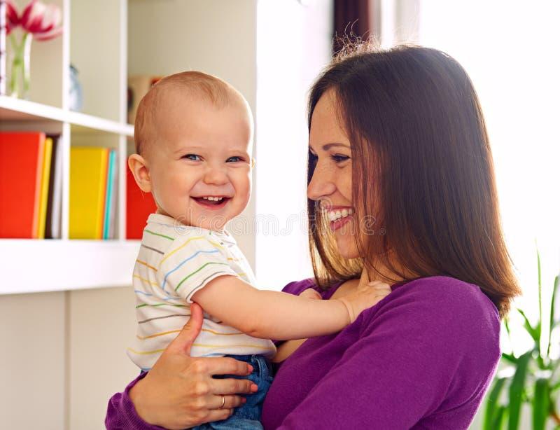 Mulher que olha o miúdo de riso em casa fotografia de stock royalty free