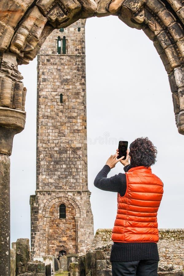Mulheres do turista que tomam imagens das ruínas de St Andrews fotografia de stock royalty free