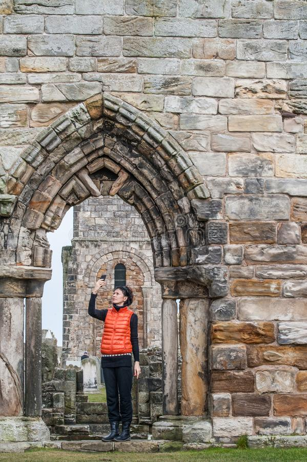 Mulheres do turista que tomam imagens do selfie das ruínas de St Andrews imagens de stock