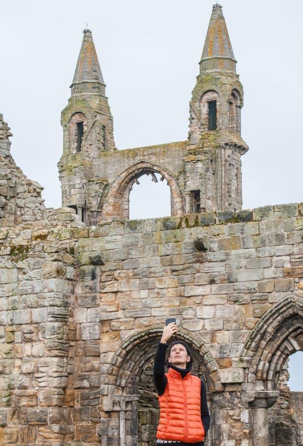 Mulheres do turista que tomam imagens do selfie das ruínas de St Andrews imagem de stock royalty free