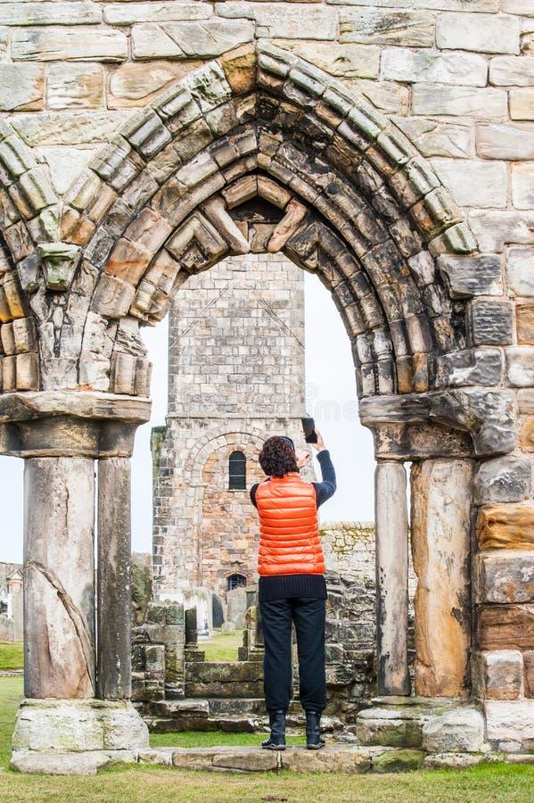 Mulheres do turista que tomam imagens do selfie das ruínas de St Andrews fotos de stock royalty free