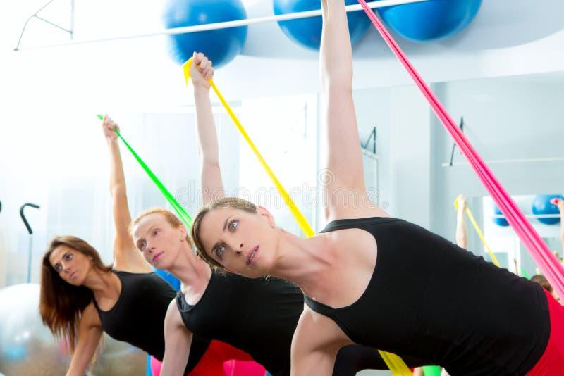 Mulheres dos pilates do Aerobics com faixas de borracha em uma fileira foto de stock