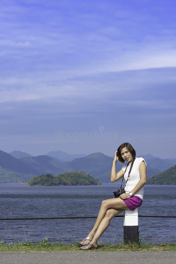 Mulheres e a câmera que senta-se em uma coluna concreta no phetchaburi da represa de Kaeng Krachan, Tailândia fotografia de stock