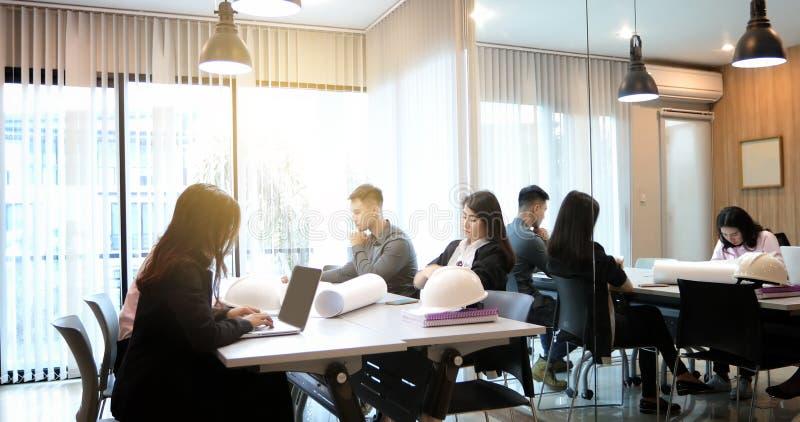 Mulheres e grupo asiáticos de negócio que usa o caderno para o encontro e os bu fotos de stock royalty free