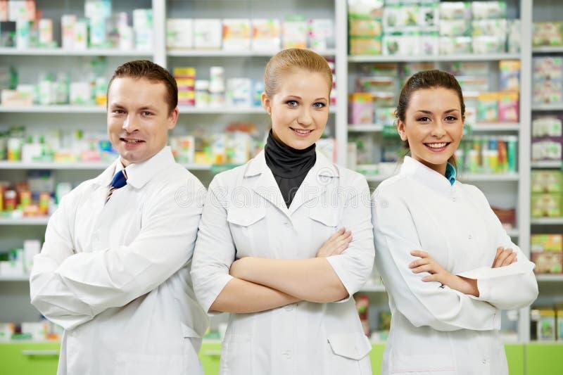 Mulheres e homem da equipe do químico da farmácia na drograria imagem de stock