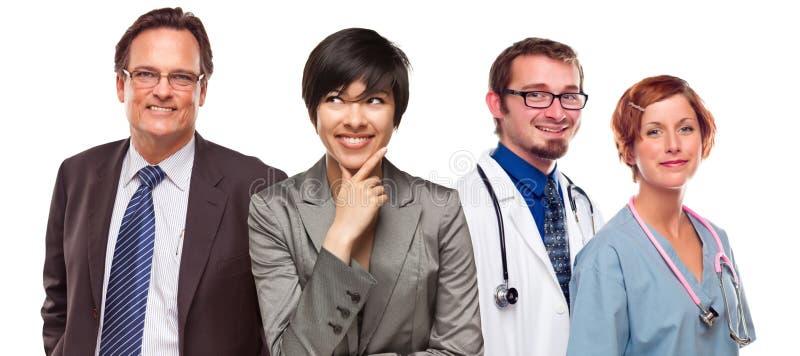 Mulheres e homem de negócios da raça misturada com doutores ou enfermeiras foto de stock