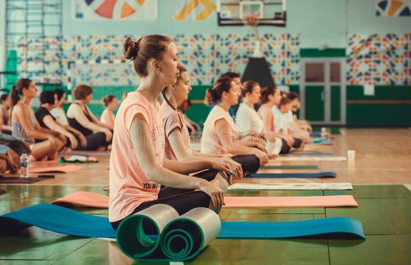 Mulheres e homens que respiram e que fazem a prática da meditação, sentando-se no asana dentro do clube de aptidão foto de stock