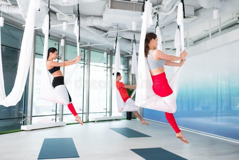 Mulheres e homens que sentem ioga praticando calma e livre do voo fotografia de stock