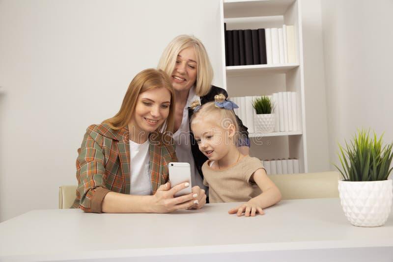 Mulheres e menina de sorriso que fazem o selfie junto foto de stock
