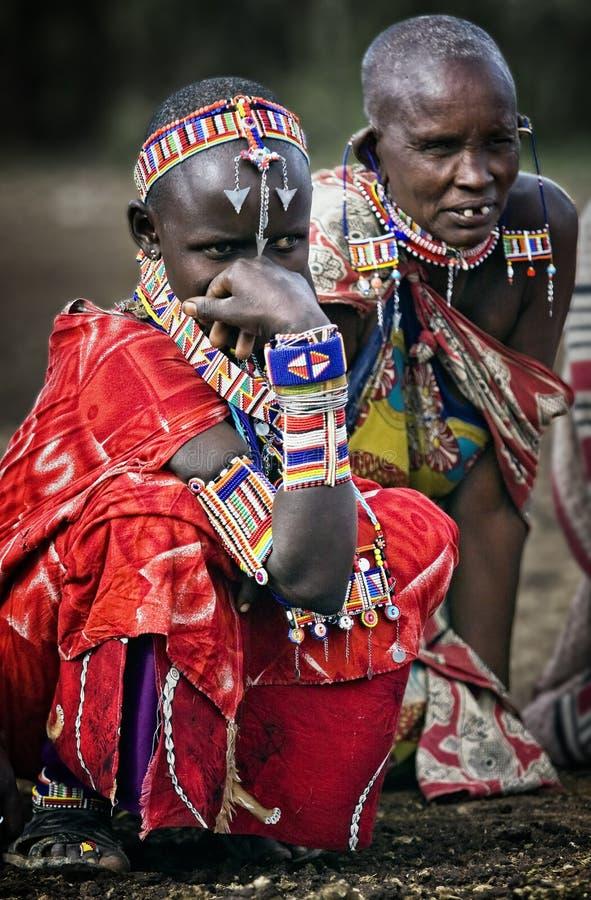 Mulheres editoriais do tribo de Massai da foto no feriado na joia e na roupa bonitas, sentando-se na terra em sua vila imagens de stock royalty free