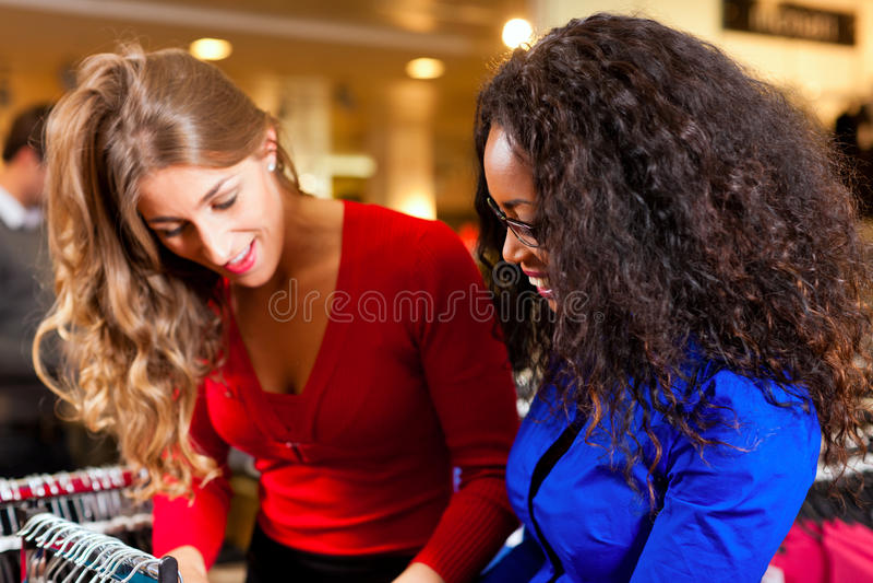 Mulheres em uma alameda de compra com roupa fotografia de stock royalty free
